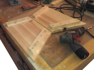 Verschrauben der Teile für die Holzschubkarre